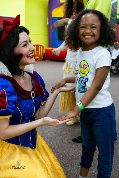 Child with down's syndrome smiling with snow white